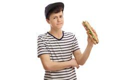 Adolescente descontentado que sostiene un bocadillo Imagen de archivo