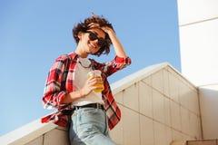 Adolescente despreocupado en gafas de sol que bebe el zumo de naranja Imagen de archivo