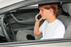 Adolescente detrás de la rueda en un teléfono celular Fotografía de archivo libre de regalías