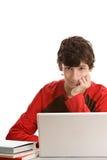 Adolescente detrás del escritorio con la computadora portátil Fotos de archivo libres de regalías