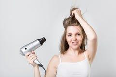 Adolescente di Ttractive che asciuga col phon i suoi capelli e che esamina macchina fotografica Fotografie Stock