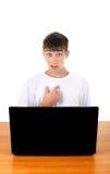 Adolescente dietro il computer portatile Fotografia Stock