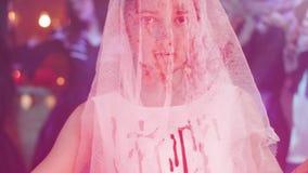 Adolescente disfarçado como uma noiva inoperante coberta no sangue com uma faca em sua mão filme