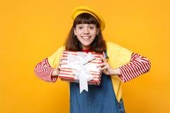 Adolescente divertido de la muchacha en la boina francesa, sundress del dril de algodón que sostienen la actual caja rayada roja  imágenes de archivo libres de regalías