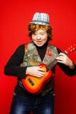 adolescente divertido del Rojo-pelo que toca poca guitarra Imagen de archivo
