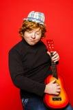 adolescente divertido del Rojo-pelo que toca poca guitarra Imágenes de archivo libres de regalías