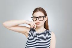 Adolescente divertido en los vidrios que hacen el bigote con su finger Imagenes de archivo