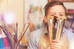 Adolescente divertido que juega con los cepillos mientras que presenta para la cámara Fotografía de archivo libre de regalías