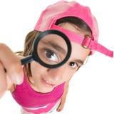 Adolescente divertido que mira a través de una lupa Foto de archivo