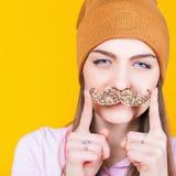 Adolescente divertido que sostiene el bigote para el partido Imagenes de archivo