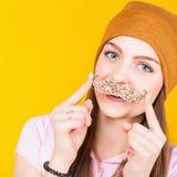 Adolescente divertido que sostiene el bigote para el partido Foto de archivo libre de regalías
