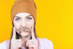 Adolescente divertido que sostiene el bigote para el partido Fotos de archivo libres de regalías