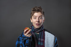 Adolescente divertido que sostiene una manzana Imagen de archivo