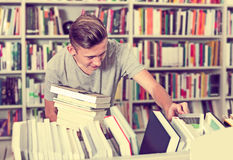 Adolescente do menino que escolhe o novo livro na loja Foto de Stock Royalty Free