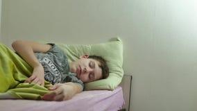 Adolescente dormido en cama El dormir interior lanudo cansado del adolescente del hombre almacen de metraje de vídeo