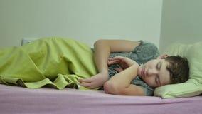 Adolescente dormido en cama El dormir interior adolescente lanudo cansado del muchacho almacen de video