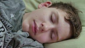 Adolescente dormido en cama El dormir lanudo cansado del adolescente del hombre dentro almacen de video