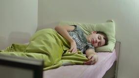 Adolescente dormido en cama El dormir lanudo cansado del adolescente del hombre dentro almacen de metraje de vídeo