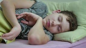 Adolescente dormido en cama El dormir lanudo cansado del adolescente interior metrajes