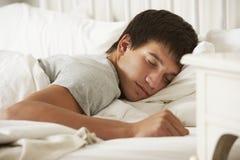 Adolescente dormido en cama en casa Imagen de archivo libre de regalías