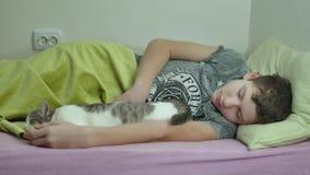 Adolescente dormido en cama sirva dentro dormir adolescente lanudo cansado del muchacho y el gato del animal doméstico almacen de video