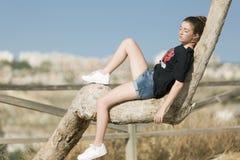 Adolescente dormido encima de un árbol Imagenes de archivo