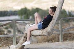 Adolescente dormido encima de un árbol Foto de archivo