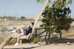 Adolescente dormido encima de un árbol Imagen de archivo
