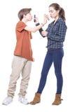 Adolescente dos que besa mutuamente sus teléfonos móviles Imagen de archivo libre de regalías