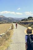 Adolescente dos que camina en una calle en paisaje mediterráneo Foto de archivo