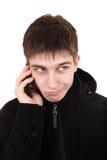 Adolescente dudoso con el teléfono móvil Imagen de archivo libre de regalías