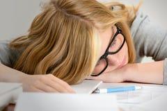 Adolescente durmiente del estudiante que miente en la tabla Foto de archivo