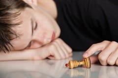 Adolescente durmiente que lleva a cabo el pedazo de ajedrez del empeño Fotos de archivo