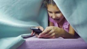 Adolescente e cão da menina sob um jogo geral da noite em um smartphone a menina antes da cama encontra-se na cama que surfa sobr filme