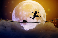 Adolescente e gatto che camminano con il pallone sulla corda stretta sopra le nuvole Fotografia Stock