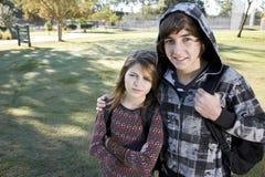 Adolescente e giovane sorella con gli zainhi del banco Immagine Stock Libera da Diritti
