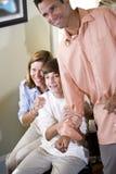 Adolescente e pais em casa que olham excitados Fotografia de Stock