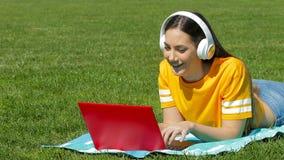 Adolescente e que aprende con un ordenador portátil en la hierba
