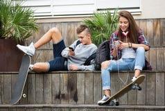 Adolescente e sua amiga com smartphones Imagens de Stock Royalty Free
