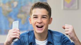 Adolescente eccitato che guarda la partita in tensione di sport sulla TV, fan di campionato del mondo stock footage