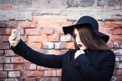 Adolescente elegante con el lápiz labial negro y el sombrero negro Imagen de archivo libre de regalías