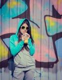 Adolescente elegante en gafas de sol coloridas que bebe el juce cerca de g Fotografía de archivo