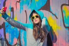 Adolescente elegante en las gafas de sol coloridas que presentan cerca de pintada Imagen de archivo libre de regalías