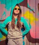 Adolescente elegante en las gafas de sol coloridas que presentan cerca del fragmento Imagenes de archivo