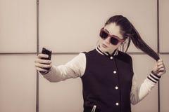 Adolescente elegante en las gafas de sol rojas que toman el autorretrato Fotografía de archivo