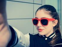 Adolescente elegante en las gafas de sol rosadas que sacan el autorretrato Foto de archivo