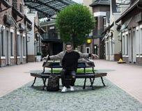 Adolescente elegante en una calle de la ciudad que se sienta en un banco Foto de archivo