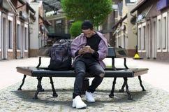 Adolescente elegante en una calle de la ciudad que se sienta en un banco Imágenes de archivo libres de regalías