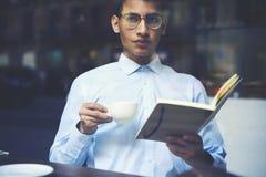 Adolescente elegante que goza de la taza de café y que mira lejos Fotografía de archivo libre de regalías