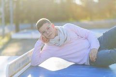 Adolescente elegante que miente sobre una tabla en un parque de la ciudad en la puesta del sol Fotografía de archivo libre de regalías
